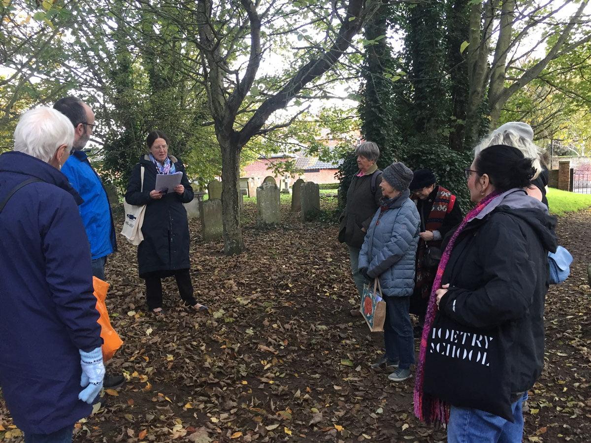 Sue Wallace-Shaddad reading in a churchyard